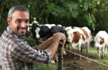 Farmer by the fenced corral holding cattle turns to the camera smiling