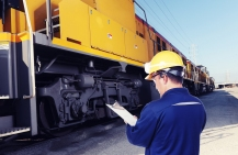 Inspector in a yellow hard hat holding a clipboard in front of a yellow train car