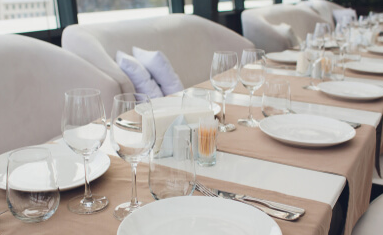 Restaurant table set up with plates, glasses and napkins